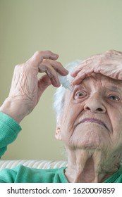 a senior woman applying eyedrops into her eyes by herself at home