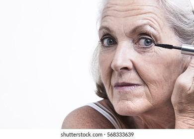 Senior woman applying mascara
