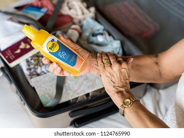 Senior woman applying sunscreen on her arm