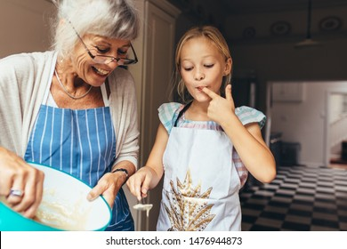 Senior woman in apron making batter for cake. Little girl tasting cake batter standing in kitchen with grandmother.