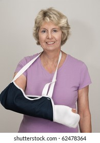 Senior woman with arm in cast and sling after injury or surgery. Gray background.