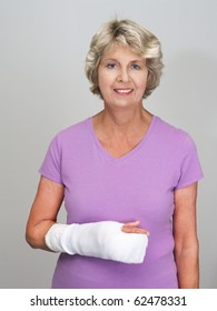 Senior woman with arm and hand in cast after surgery or injury. Gray background.