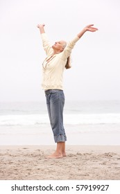 Senior Woman With Arms Outstretched On Winter Beach