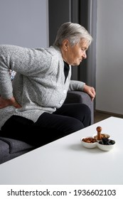 Senior woman with back pain sitting on sofa at home and trying to get up