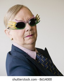 Senior woman in a baggy man's suit wearing funny glasses