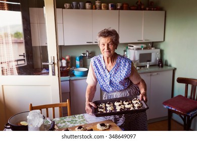 Senior woman baking pies in her home kitchen.  Filling the buns with cottage cheese and jam.