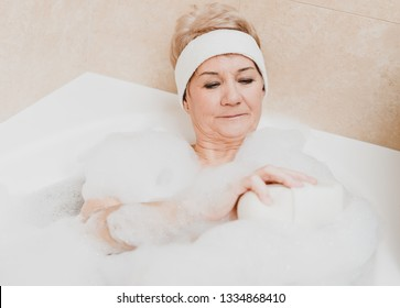 Senior woman is bathing in hot water and foam. She is caring for body.