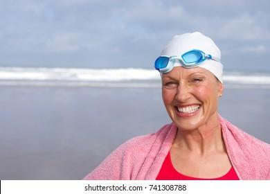 Senior woman in bathing suit smiling at beach