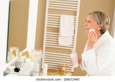 Senior woman in bathroom clean face milk lotion looking mirror