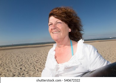 senior Woman at the beach under blue sky smiling