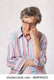 Senior woman between 70 and 80 years old is thinking about something. Gray  background