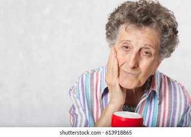 Senior woman between 70 and 80 years old and a box of face cream