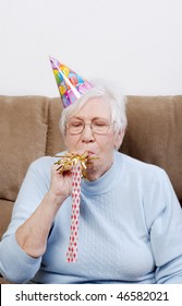 senior woman with birthday hat blowing a noise maker