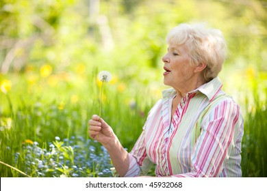 Senior woman blowing dandelion at the meadow
