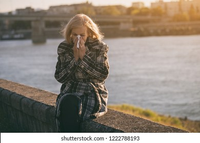 Senior woman blowing nose while sitting by the river.Toned image