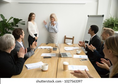 Senior woman boss introducing new female worker making compliment for work result while employees applauding at group meeting, team congratulating coworker with promotion, welcome recognition concept