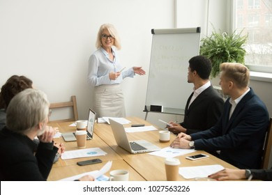 Senior woman boss leading corporate team meeting presenting team goals, smiling aged businesswoman company leader or business teacher giving presentation coaching diverse employees group in boardroom