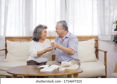 senior woman brink glass of milk to older husband in living room while he working or reading. self-quarantine from Coronavirus outbreak, love and take care family, healthy lifestyle insurance concept
