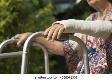 senior woman broken wrist using walker in backyard.