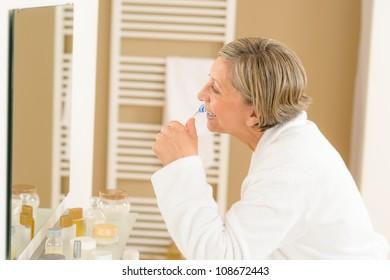 Senior woman brushing teeth in front of bathroom mirror