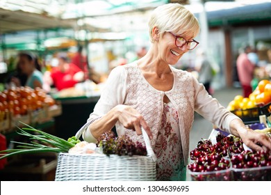 Senior woman buying fresh fruits and vegetables at the local market
