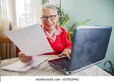 Senior woman calculating her expenses, dissatisfied with the bills and the numbers