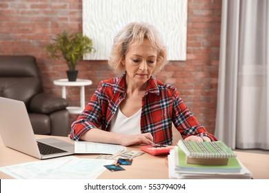 Senior woman calculating taxes at home