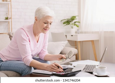 Senior woman with calculator and bills counting dollar money at home, free space