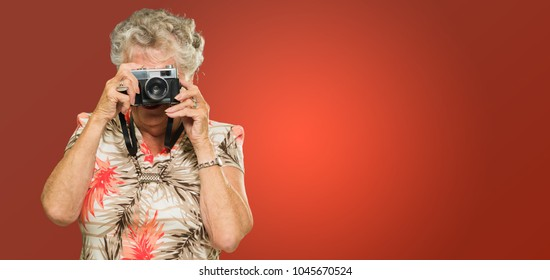 Senior Woman Capturing Photo Isolated On Red Background