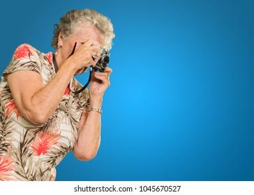 Senior Woman Capturing Photo Isolated On Blue Background