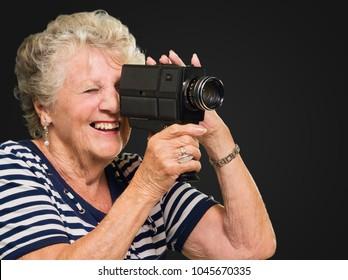Senior Woman Capturing Photo On Black Background