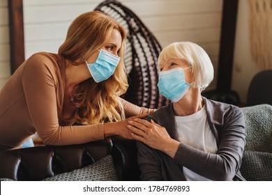 Senior woman with caring daughter at home. Females wearing medical masks.