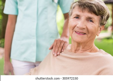 Senior woman and caring nurse in the garden