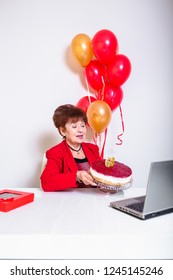 Senior woman celebrating her birthay at home with cake, ballons and confetti