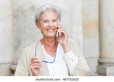 Senior woman with cell in front of a wall