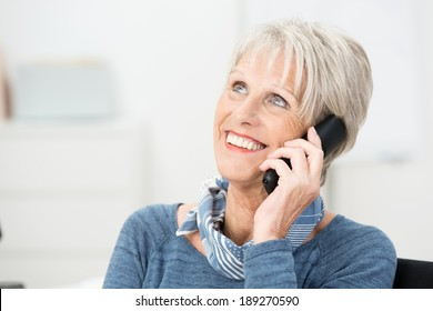 Senior woman chatting on her mobile phone smiling with delight as she listens to the conversation