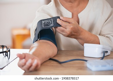 Senior woman is checking blood pressure and heart rate with digital pressure gauge by herself at home.Older woman taking care for health. Health and Medical concept.