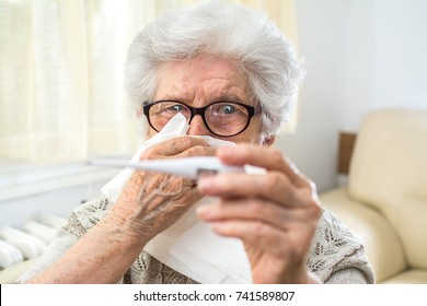 Senior woman checking body temperature with thermometer and blowing nose.