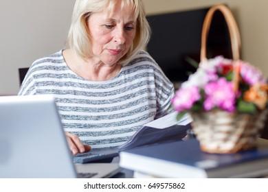 Senior woman checking his bills at home