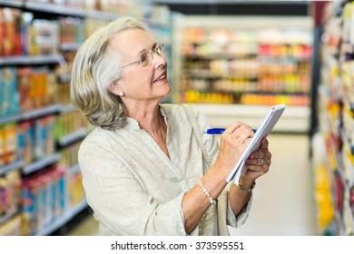 Senior woman checking list at the supermarket