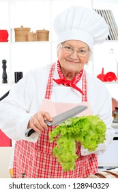 Senior woman chef cook holding lettuce in the kitchen.