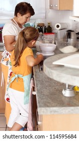 Senior woman and child baking together