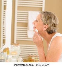 Senior woman clean face with cotton pad  looking bathroom mirror