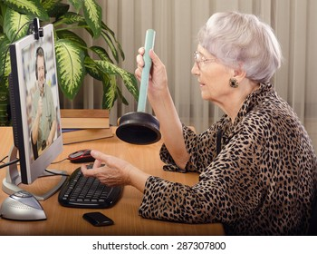 Senior woman is clearing how to fix a clogged toilet. She sits on front of computer monitor and asks to virtual plumber. On the screen, plumbing expert explains how to use a plunger toilet.