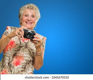 Senior Woman Clicking Photo On Blue Background