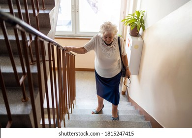 Senior woman climbing staircase with difficulty