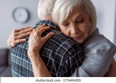 senior woman with closed eyes embracing husband sick on dementia