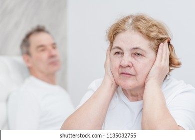 Senior woman closed her ears with her hands, so as not to hear the deceit of her husband