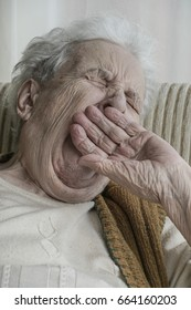 senior woman closing her mouth with hand while yawning