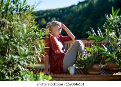 Senior woman with coffee sitting outdoors on terrace, resting.